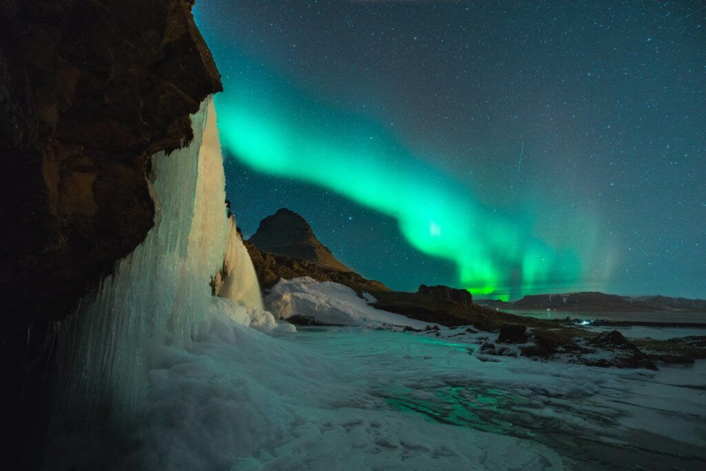 An idylic landscape close to the North Pole, with mountains, ice and snow, and the northern lights that give the sky a green shade.